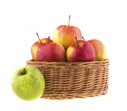 Red and green apples in a wicker baskets Stock Image