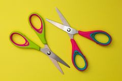 Red and green baby scissors isolated on a yellow background stock photography