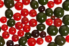 Red and green beads. Red and green beads lie on a flat surface of a white color Stock Photo
