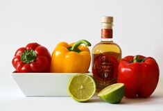Red and Green Bell Pepper Inside White Ceramic Tray Near to Bottle and Lemon stock photo