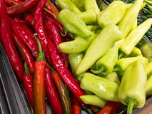 Red and green bell pepper in supermarket. Chili royalty free stock images