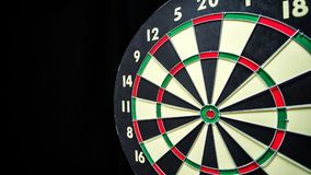 Dartboard on Black. Red, green, black, and cream dartboard on black with copy space on left Royalty Free Stock Image