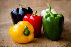 Red, green, black, white and yellow bell peppers. On sackcloth  background Stock Photo