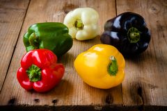Red, green, black, white and yellow bell peppers. On wooden background Stock Images
