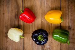 Red, green, black, white and yellow bell peppers. On wooden background Stock Photos