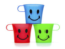 Red, green and blue cups with smiley faces Stock Photos
