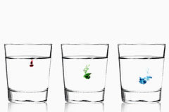 Red Green Blue diffusion. Red, green and blue food color diffusing into three glasses of water stock image