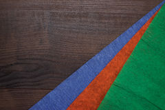 Red green and blue jammed paper on wooden. Background Royalty Free Stock Photography