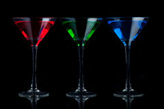 Red, green, and blue martini glasses. A red, a green, and a blue martini glass on a black background with a mirrored foreground Stock Image