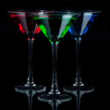 Red, green, and blue martini glasses. A red, a green, and a blue martini glass on a black background with a mirrored foreground Royalty Free Stock Photos