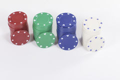 Red, green, blue and white poker chips. With single disks in front of them over white background. Includes copy space Royalty Free Stock Image