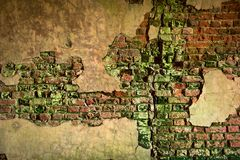 Brick wall with peeling plaster. Red-green brick wall with peeling plaster Stock Image