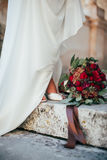 Red-Green bridal bouquet at the feet of the bride Royalty Free Stock Photos