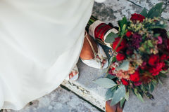 Red-Green bridal bouquet at the feet of the bride Stock Photos
