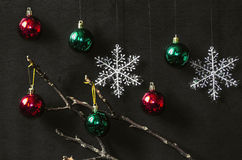 Red and green bright balls with snowflakes. On wooden  black background Stock Photography
