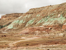 Red, green and brown rock layers eroding. Layers of red, green and brown rock and mudstone have weathered to create a colorful texture in a desert landscape of Stock Image