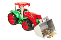 Red and green bulldozer with coins Royalty Free Stock Images