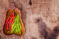 Red and green Chili Peppers in bowl on wooden background Royalty Free Stock Photos