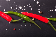 Red and green chili peppers, coarse salt on the chalkboard. tint Royalty Free Stock Images