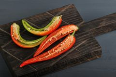 Red and green chili peppers cut in half on wooden Board. Red and green chili peppers cut in half on a wooden Board Royalty Free Stock Photos