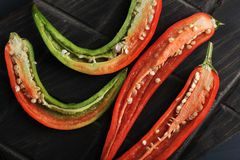 Red and green chili peppers cut in half on a wooden Board. Top view Stock Photo