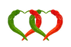 Red and green chili peppers in love. Hearts composed of hot pepp Stock Images