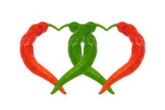 Red and green chili peppers in love. Hearts composed of peppers. Royalty Free Stock Photos
