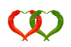 Red and green chili peppers in love. Hearts composed of peppers. Stock Photo