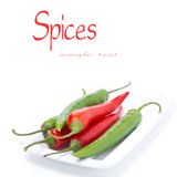 Red and green chili peppers on the plate, isolated Royalty Free Stock Photography