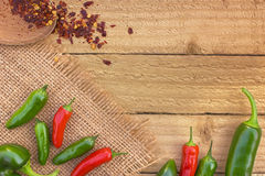 Red and green chili peppers on a rustic background viewed from the top with copy space royalty free stock photos