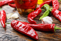 Red and green chili peppers with spices are lying on the table. Bank of canned chili peppers, lies next to the garlic, bay leaf, olive oil and raw hot peppers Royalty Free Stock Image