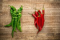 Red and green chili peppers on wooden background Stock Images