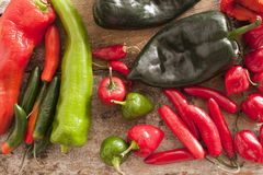 Red and Green Chili Peppers on a Wooden Table. High Angle View of Assorted Red and Green Chili Peppers on a Rustic Wooden Table Royalty Free Stock Images