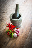 Red and green chili and red onion and garlic and stone mortar on Stock Photo