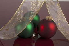 Red and Green Christamas balls. With Ribbon on maroon reflective surface royalty free stock image