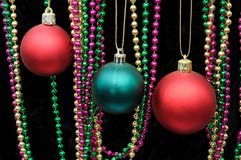 Red and green Christmas baubles. Red and green plastic Christmas baubles with colourful beads against a black background Royalty Free Stock Photo
