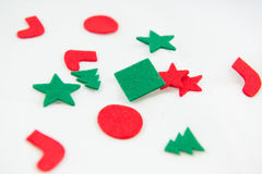 Red Green Christmas Embellishments. Red and green felt xmas embellishments for scrap booking, card making and crafts isolated on white background. Christmas fun Stock Image