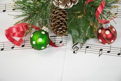 Christmas ornaments on music. Red and green Christmas ornaments and ribbon with pine on sheet music royalty free stock photos