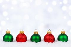 Red and green Christmas ornaments in snow with twinkling background Stock Image