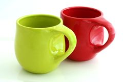 Red and Green Coffee Mugs. Two coffee mugs isolated on white - one red, one lime green stock image