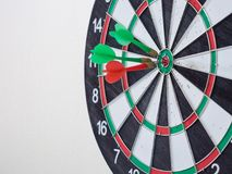 Red and green dart arrow hitting on center target. stock photography