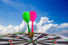 Red and Green Dart arrow hitting in the target center of dartboard stock images