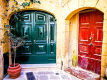 Red and Green Doors Gozo. Red and green doors in gozo malta typical stone building alley royalty free stock photos