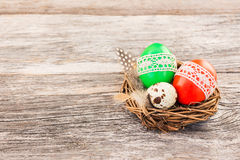 Red and green Easter eggs decorated with lace in small decorative nest. Selective focus Stock Photos