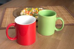 Red and green empty tea or coffee cups on wooden background closup Royalty Free Stock Photo
