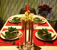 Red and green festive table. Festive holiday table with decorated napkins and flower arrangement Royalty Free Stock Photography