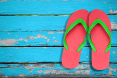 Red and green flip flop on blue wood. Red and green flip flop sandals on blue wood Royalty Free Stock Photos