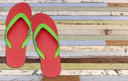 Red and green flip flop sandals on old wood Stock Photos