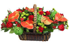 Red-and-green floral arrangement in a wicker basket. Royalty Free Stock Photos