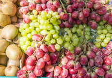 Red and green grapes and kiwifruit in a market stock photo